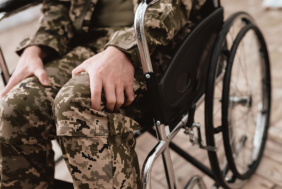 veteran with cane in wheelchair